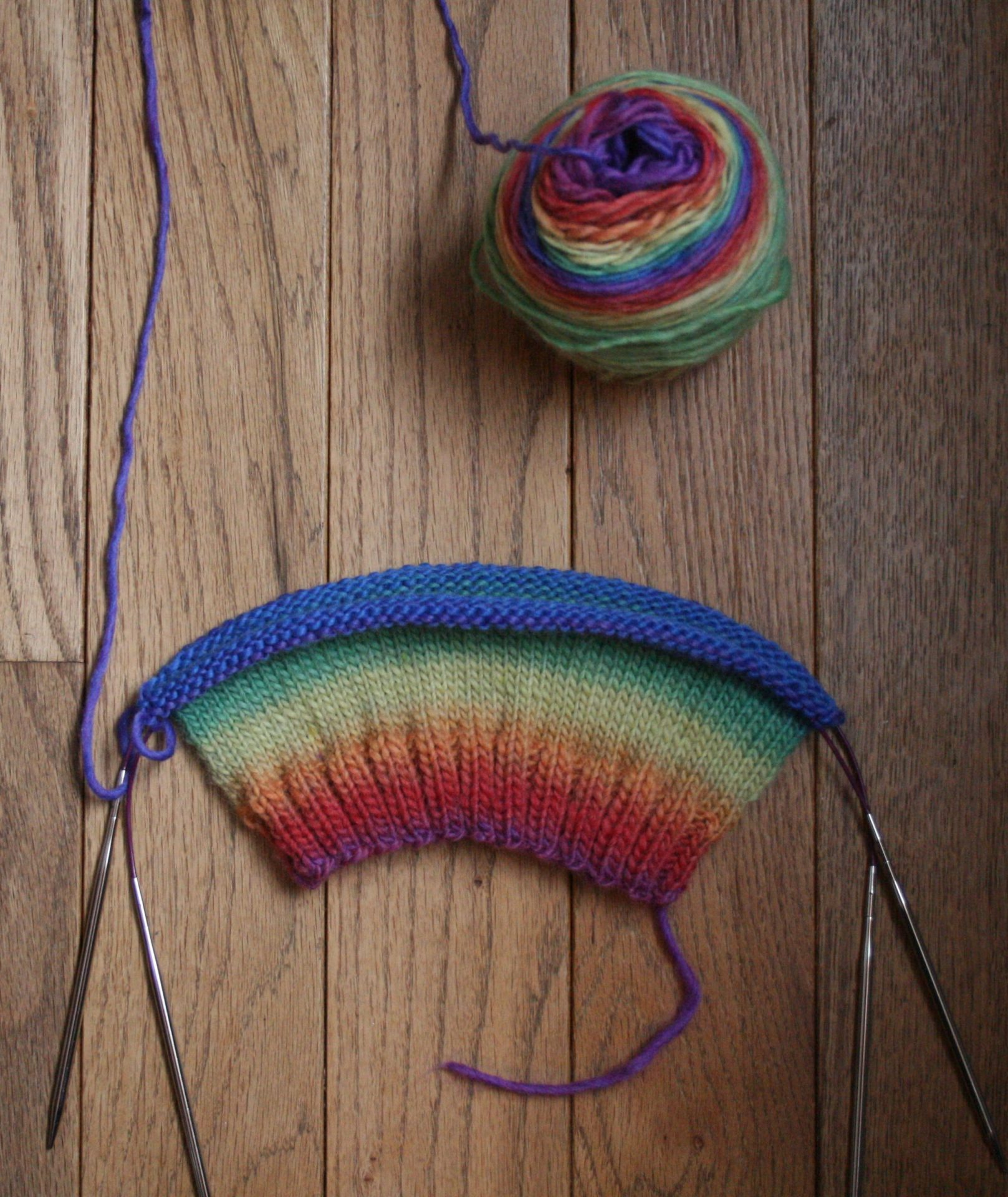 Photo of rainbow earflap hatting being knit.