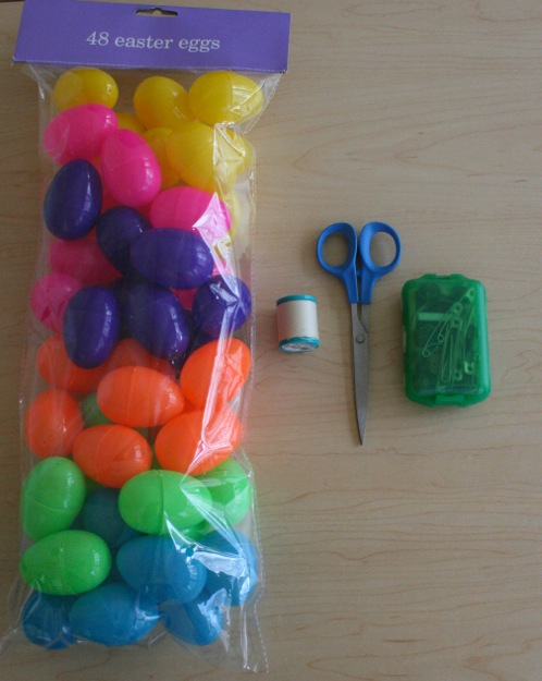 Photo of plastic eggs, scissors, and string.