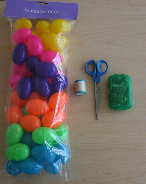 Photo of plastic eggs, scissors, and string.